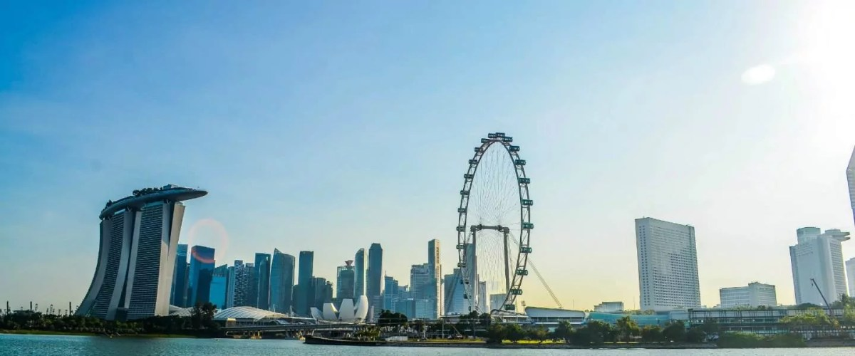 A panoramic view of the Marina Bay Sands, the Singapore Flyer, and Singapore skyline during daytime.