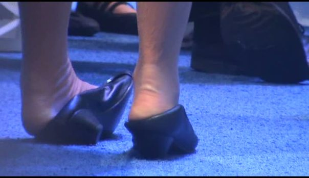 auto-show-model-crushes-down-the-backs-of-her-mid-heel-pumps-to-try-to-ease-severe-foot-painexcellent-pain-image