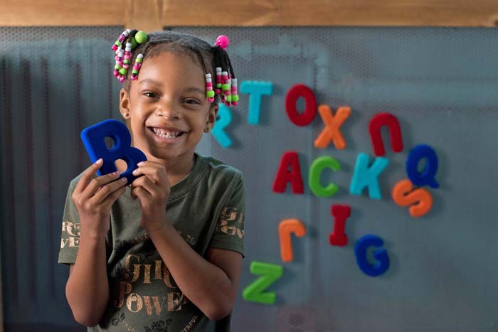 Female child holding letter B in front of a wall of magnetic letters