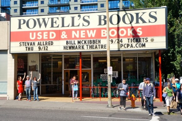 Laura Stanfill, Stevan Allred, and Gigi Little stand beneath Stevan's name on the marquee at Powell's.