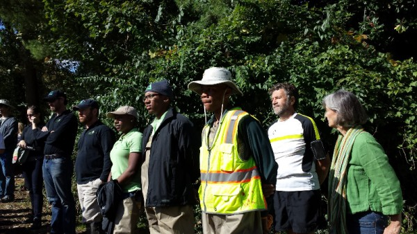 A Green Team student in a yellow vest and waders, with Groundwork Anacostia