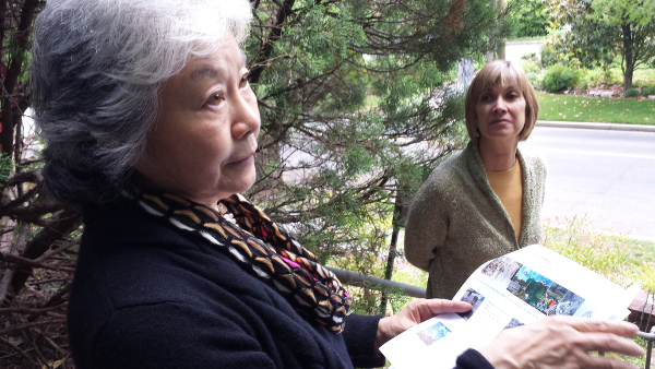 Setsuko Ono, right, showing visitors a handout with thumbnail photos and titles of the pieces on display.