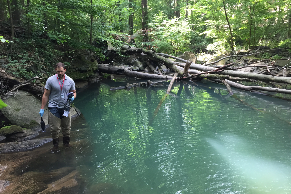 DOEE samples and analyzes Soapstone Creek surface water.  (Courtesy Julia Robey Christian, DOEE)