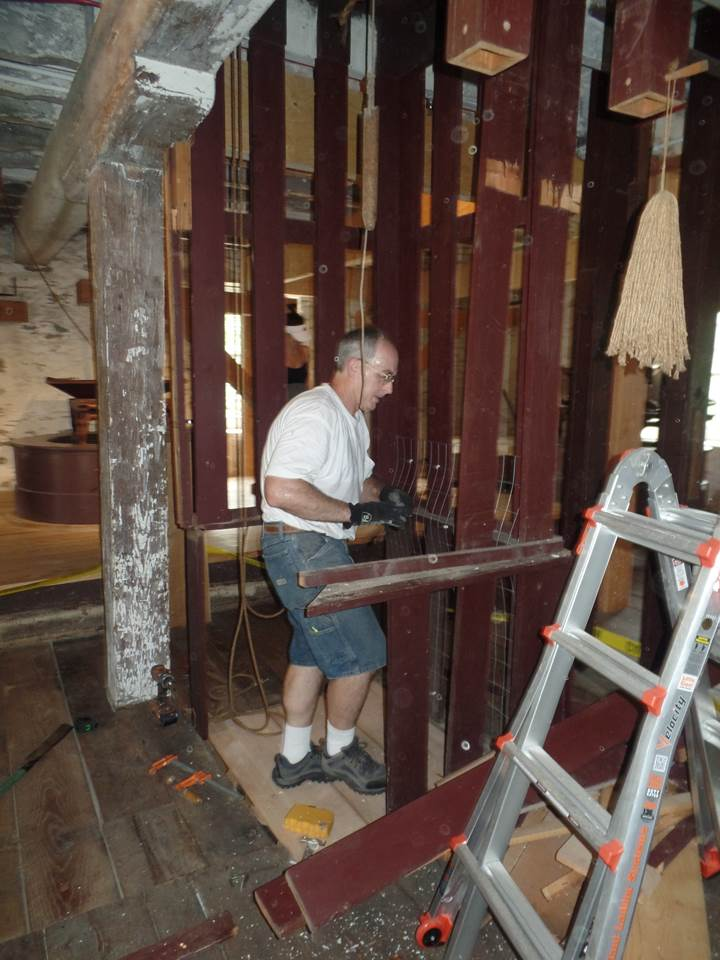 Mill restoration expert Steve Ortado removing the circa-1970s cage from the barrel hoist. (photo courtesy of Deborah Dougherty)