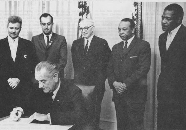 President Lyndon Baines Johnson signing the DC Public Education Act in November 1966. Onlookers include Sen. Wayne Morse (D-Ore.),  main supporter of establishing FCC, Mayor Walter Washington, and Dr. Cleveland Dennard, slated for presidency of WTI. (photo courtesy UDC Archives)