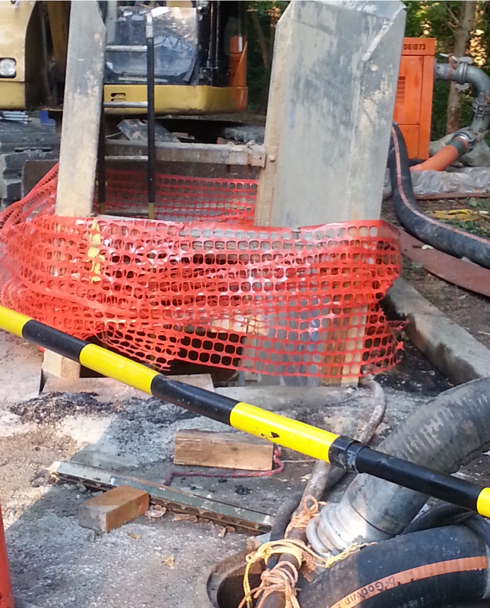 In the foregound are both bypass hoses. In the background is one of the bypass pumps. And in the center - just downstream from the manhole - are two concrete shoring panels and orange construction fencing for the work pit. (photo by Marjorie Share)