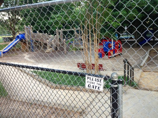 The Forest Hills playground on June 9th, the first day of demolition. Seen here: The construction fence. Not seen (anymore): The toys and wood chips.