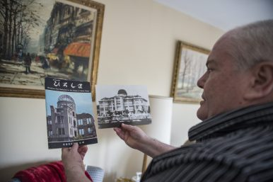 Armstrong holds pamphlets from the A-Bomb dome that contain his poem. (By ALEXA ROGALS/Staff Photographer)