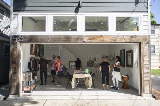 Attendees look through artwork hung on the walls at 519 Beloit Avenue on Saturday, Aug. 24, 2019, during the annual Garage Galleries throughout Forest Park. | ALEXA ROGALS/Staff Photographer