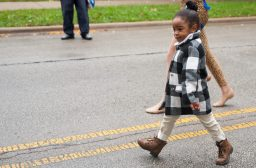A little girl mimicking the dancers in the Proviso East Homecoming parade on Saturday in Maywood. | Photo by Shanel Romain