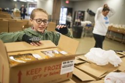 Emily Lyons helps fill boxes during the Community Center's annual Thanksgiving meal delivery on Nov. 27