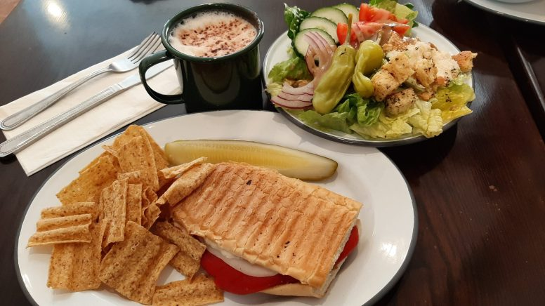 Seph's Sweets Lunch 1: Seph's Sweets is offering a mix and match lunch special throughout Elmwood Park's Restaurant Week. Here a hot vegetarian panini is shown with a side salad, chips and a pickle. Served alongside a house made latte this generous lunch is 0.25 between February 21st-March 1st. Photo by Melissa Elsmo.