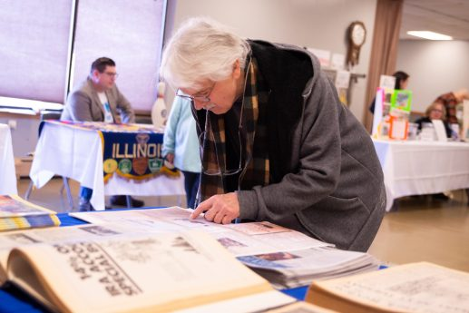 Forest Park resident David Woyman reading from archived pages of the Forest Park Review at the Leap Day History & Community Festival in Forest Park on Saturday. | SHANEL ROMAIN/Contributor