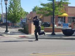 A police officer runs across Madison Street after a bank robbery at the corner of Desplaines Avenue and Madison Street on May 31.