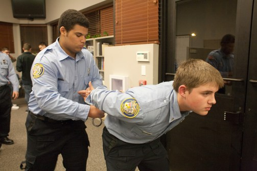 Book'em Danno: Explorer scouts Aaron Wimbush, left, and Connor Solms practice handcuff techniques at a recent meeting at the Forest Park Police Department.Photos by DAVID PIERINI/Staff photographer