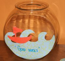 """Our """"Good Works"""" fish bowl we are filling up throughout Lent with our fish notes of good things we did during the day: Sticking up for a classmate, smiling at someone who looks anxious, donating to a local charity, shopping local."""