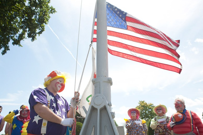 Cool Beanz raises a clown banner and the American Flag to begin a ceremony that honored dead circus artists buried at Woodlawn Cemetery in Forest Park.