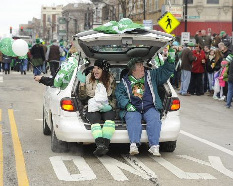 Alexa Stisevic and Bridget Dowdle wave out of the back of a station wagon during the Forest Park St. Patrick's Day Parade. (Jennifer Wolfe/contributor)