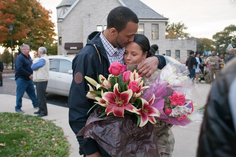 Victor Gavin greets his girlfriend, Staff Sgt. Samantha Villafuerte, with a kissing embrace and large bouquet of flowers. Members of the Forest Park U.S. Army Reserve 300th Human Resources Company were welcomed home from Afghanistan Thursday at The Park. (David Pierini/staff photographer)