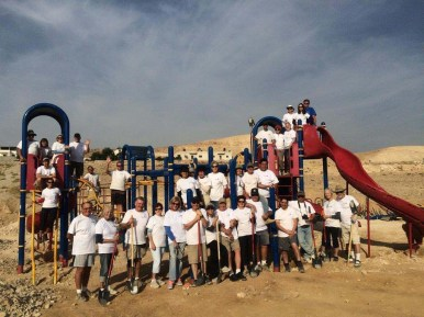 Volunteers from Kids Around the World stand in front of Forest Park's old playground equipment, lovingly refurbished and re-installed in a Palestinian playground. (Courtesy Rachell Entler)