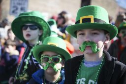 A mustachioed Bradley Kos (center), 4, and James Long (right), 7, watch as the Forest Park St. Patrick's Day Parade marches down Madison Street on Saturday. (CHANDLER WEST/Staff Photographer)