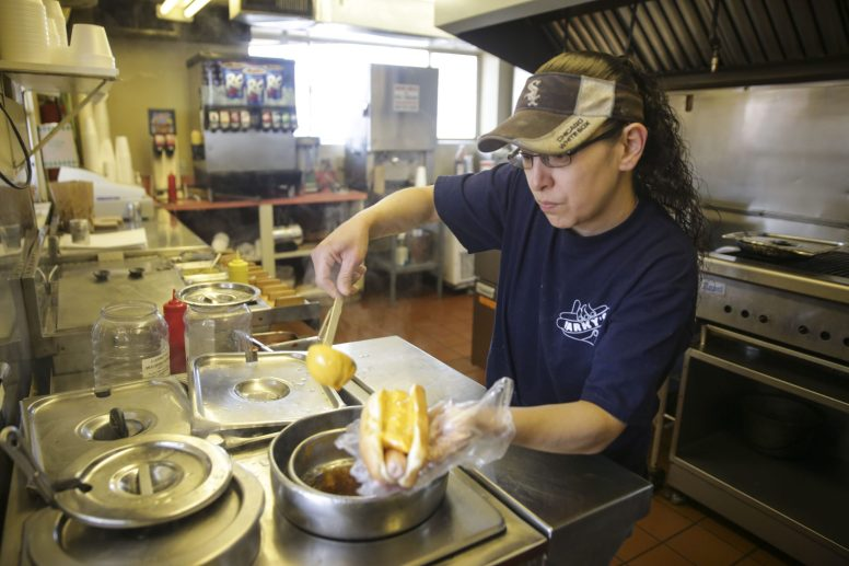 Sonia Flores, owner of Parky's Hot Dogs, customizes a hot dog. (CHANDLER WEST/Staff Photographer)