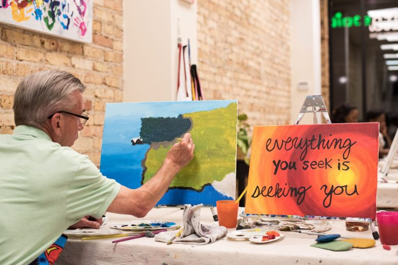 John Rice adds texture to his painting of an Irish seaside scene next to Jessica Jordan's completed painting. | MAX HERMAN/Contributor