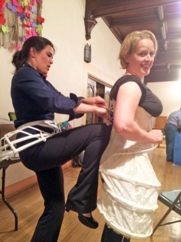 """Alison Kelly (CFO founder, plays """"Belotte"""") helping Rachel Olson (""""Madeleine"""") into her corset in rehearsal for Madame Pompadour. 
