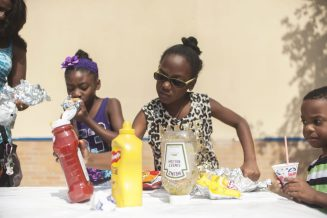 Jaylon Dixon gets ready to put some ketchup and mustard on her hot dog. | William Camargo/Staff Photographer