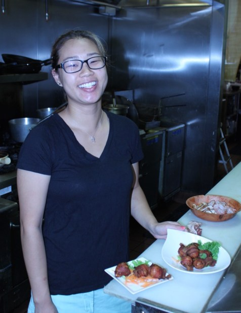 Smiling Julie Yu cooking up delicious food for her guests.