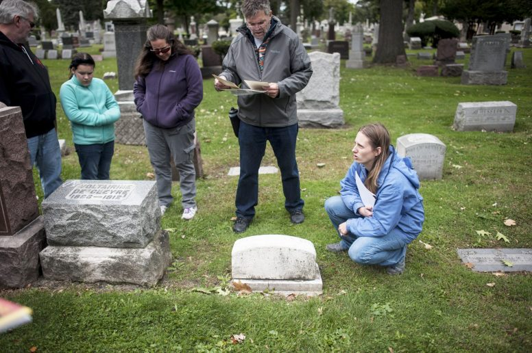 Diane Grah, executive director of the Forest Park Historical Society (kneeling) and labor historian Mark Rogovin (to her right), led a tour of the Haymarket Memorial and the graves of other noted labor activists at Forest Home Cemetery on Saturday, Oct. 3. | William Camargo/Staff Photographer