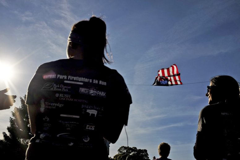 Runners listen to Cece Mo sing the National Anthem before the start of the Firefighters 5K in Forest Park on Oct. 10.   William Camargo/Staff Photographer
