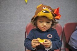 Elouise Billingsley, dressed as a Chicago Bear, works on an orange slice. | William Camargo/Staff Photographer