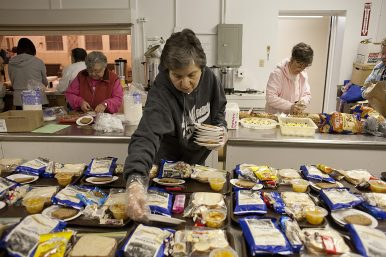 JoAnn Marra places plates of bread on food trays that fed 48 men, women and children staying at the shelter in St. John Lutheran Church. | File 2014