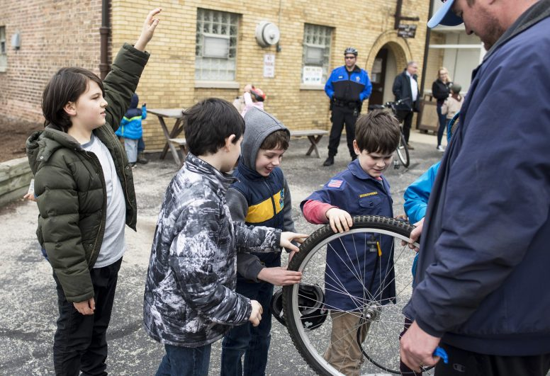 Scouts learn how to fix a flat tire and check a fixed tire at St. John Lutheran Church in Forest Park on March 12. | William Camargo/Staff Photographer