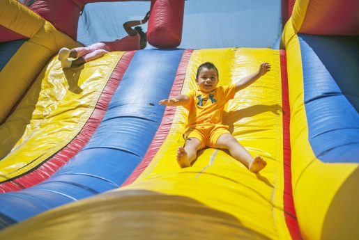 Johnathan Velez slides down a inflatable playhouse during the All School Picnic at The Park on May 19. | William Camargo/Staff Photographer