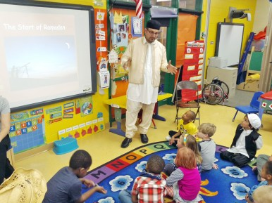 Imad Tarhoni co-taught a presentation with ELL teacher, Jill Torres, about Ramadan during a preschool class at Garfield Elementary School. Bayan, Tarhoni's son (far right) is aslo in the class. Tarhoni's wife, Sarah, made special treats for the class to share. | Courtesy Jane Catezone