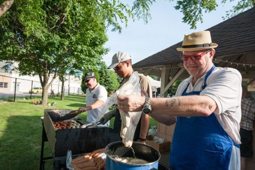 Oliver Pergrams (right) gets help from son Alex while preparing th?ringer and bratwurst sausages for German Fest at The Grove on June 11. | MAX HERMAN/Contributor