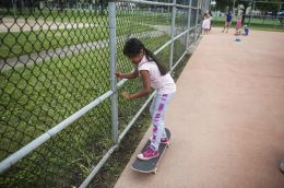 Carly Figueroa uses the fence to steady herself. | William Camargo/Staff Photographer