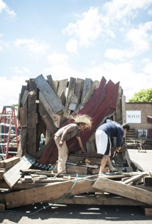 Artists work on a wooden Buddha at Re-Use Depot in Maywood in July. | William Camargo/Staff Photographer