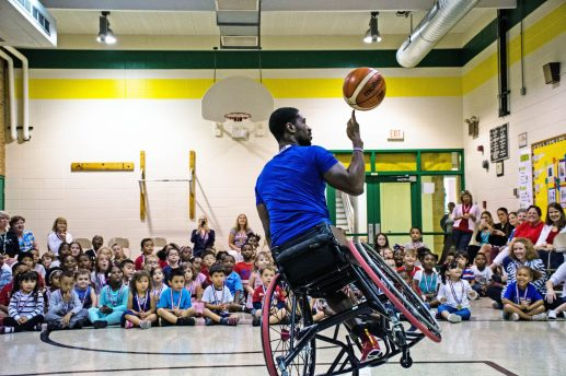 Brian Bell, a Paralympian gold medalist for Team USA, wows the students at Garfield Elementary School with moves he used during basketball games at the Rio Paralympics. | Photo by Sebastian Hidalgo