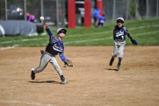 Nolan from the Forest Park Dominators throws out a player at first base during the opening game of Forest Park Little League on Saturday, May 6. | William Camargo/Staff Photographer