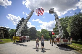 Two firefighter ladders hold a giant American flag before the start of the Forest Park Firefighters 5K in Forest Park on Saturday, June 24 at Concordia Cemetery, 7900 Madison St. | William Camargo/Staff Photographer