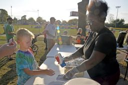 Jada Watson, of Oak Park, serves burgers and hot dogs to participants. | Alexa Rogals/Staff Photographer