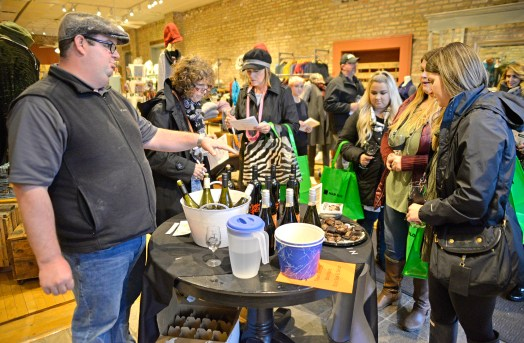 Ryan Gillian, a distributor with 90+ Cellars, talks about the wine with participants on Saturday, Nov. 4, 2017, during the annual Wine Walk and Shop at participating businesses on Madison Street in downtown Forest Park, Ill. ALEXA ROGALS/Staff Photographer