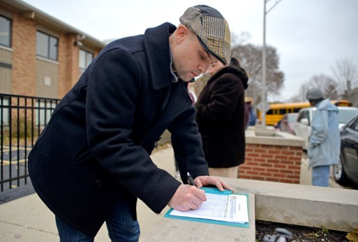 Brian Hepner signs a petition to have a stop sign installed at Jackson Boulevard and Hannah Avenue.   Alexa Rogals/Staff Photographer
