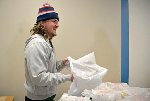 Brady Ryan, a community center counselor, packs up dinner rolls and pumpkin pies. | Alexa Rogals/Staff Photographer