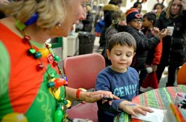 Lori Wheeles, left, with All About Fun Entertainment, gives Ryan Sherman, 3, of River Forest, a temporary dolphin tattoo on his hand on Dec. 1, during the annual Holiday Walk and Festival of Windows on Madison Street in downtown Forest Park. | Alexa Rogals/Staff Photographer