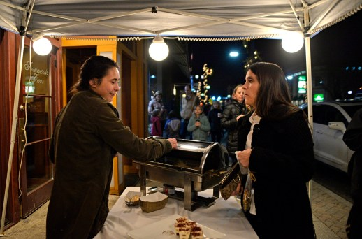 Grace Rivera, left, of Oak Park, serves ravioli to Mary Ann Brent of Forest Park, outside of Francesca's on Dec. 1, during the annual Holiday Walk and Festival of Windows on Madison Street in downtown Forest Park. | Alexa Rogals/Staff Photographer