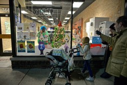 Participants walk past the Grinch window display put on by the Forest Park Review at Grand Appliance and TV on Dec. 1, during the annual Holiday Walk and Festival of Windows on Madison Street in downtown Forest Park. | Alexa Rogals/Staff Photographer